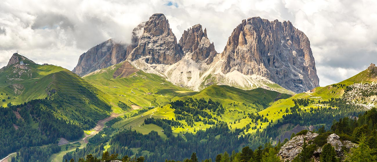 The Dolomites surrounded by green meadows and woods