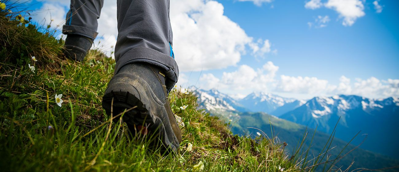 Detail of the feet of a hiker walking on a grassy slope