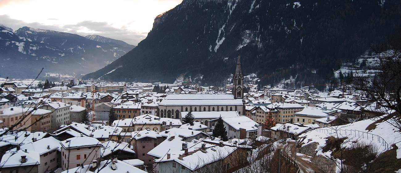A village in the Val di Fiemme in winter with the roofs of houses covered by snow