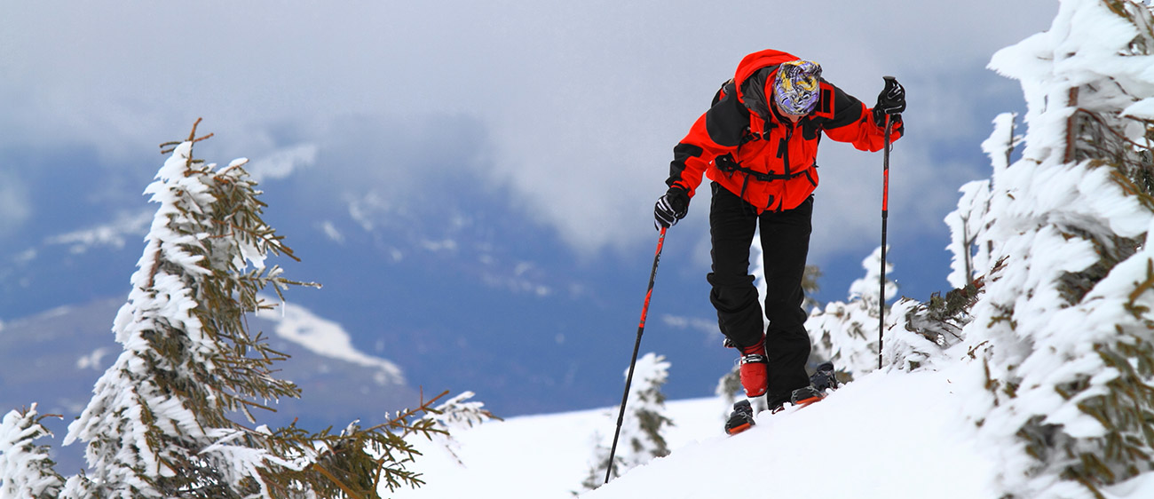 Person with red clothes and blacks makes ski mountaineering