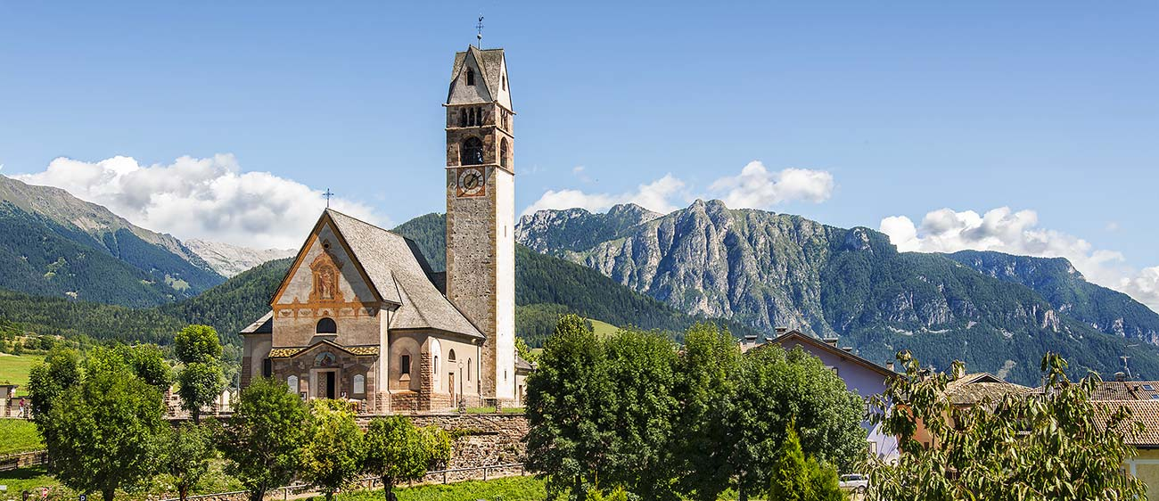 The church of the village of Carano in Val di Fiemme, surrounded by mountains