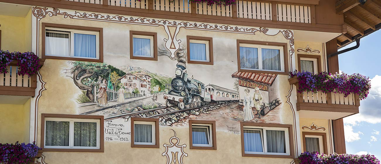 A facade of a house in the town of Predazzo painted with a train