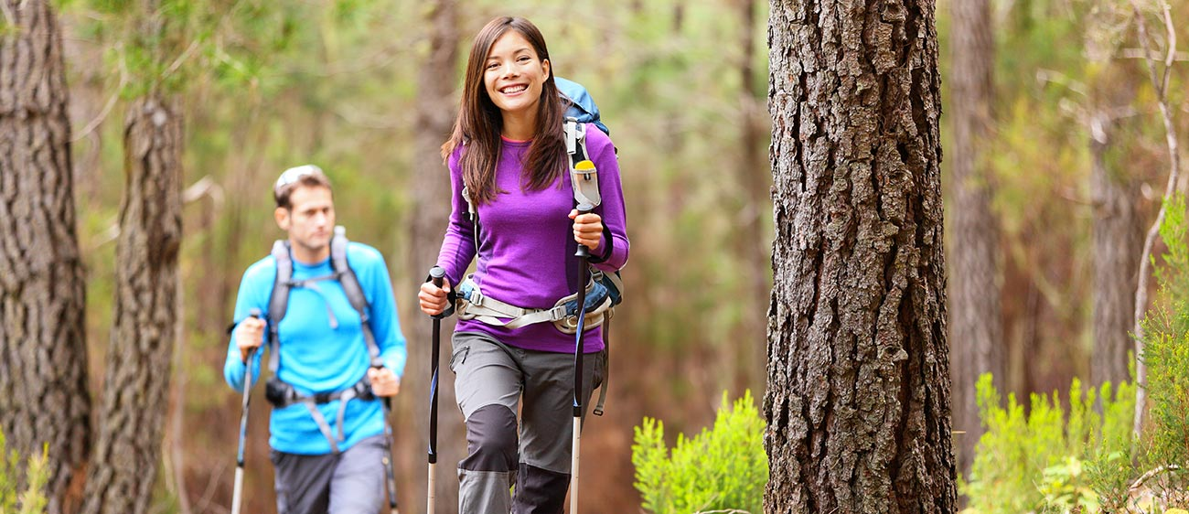 Two people do Nordic Walking in the woods