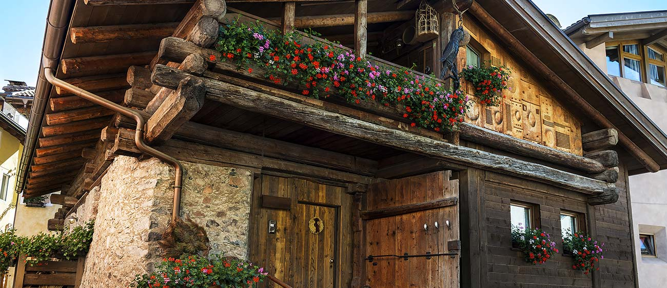 Old house of wood and masonry with geraniums on the balconies